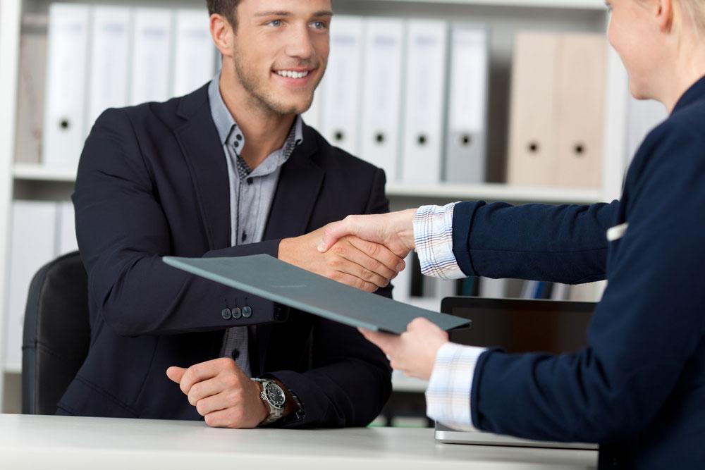 deux personnes se serrant la mains au dessus d'un bureau l'une tenant un dossier dans la main